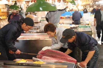 Les acheteurs observent scrupuleusement la découpe du thon
